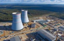 一个核电站的航测建设中 能源厂的设施和建筑 可更新的绿色能量的概念:一棵雏菊和草在残破的核能的标志 图库摄影