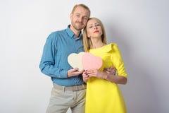 一个格子花呢上衣和苗条女孩的可爱的中年人一件黄色礼服的拿着心脏 免版税库存照片