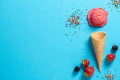 一个桃红色冰淇凌瓢的顶视图在一个奶蛋烘饼锥体的与strawber 免版税图库摄影