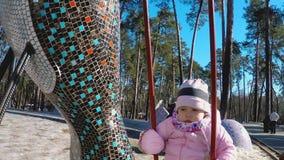 一个桃红色夹克和镶边帽子的一女孩在摇摆乘坐在有高松树的一个公园在早期的春天 股票视频