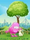 一个桃红色妖怪和一只妖怪猫在树附近 免版税库存照片