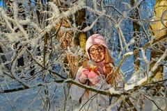 一个桃红色帽子的女孩喝被仔细考虑的酒的在冬天在森林里 库存照片
