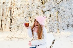 一个桃红色帽子的女孩喝被仔细考虑的酒的在的冬天为 免版税库存照片