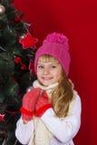 一个桃红色帽子的美丽的在微笑和寻找礼物的除夕的女婴和手套 库存照片