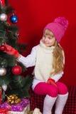 一个桃红色帽子的美丽的在微笑和寻找礼物的除夕的女婴和手套 免版税库存图片