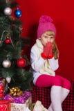 一个桃红色帽子的美丽的在微笑和寻找礼物的除夕的女婴和手套 免版税库存照片