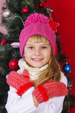 一个桃红色帽子的美丽的在微笑和寻找礼物的除夕的女婴和手套 免版税图库摄影