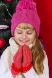 一个桃红色帽子的美丽的在微笑和寻找礼物的除夕的女婴和手套 库存图片