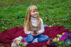 一个桃红色帽子的美丽的矮小的年轻婴孩有一个团的在他的手上 漂亮的孩子坐红色格子花呢披肩 免版税库存图片