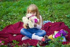 一个桃红色帽子的美丽的矮小的年轻婴孩有花的在他们的手上 库存图片