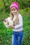 一个桃红色帽子的美丽的矮小的年轻婴孩有花的在他们的手上 免版税库存图片