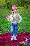 一个桃红色帽子的美丽的矮小的年轻婴孩有花的在他们的手上 免版税库存照片