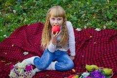 一个桃红色帽子的美丽的矮小的年轻婴孩用一个苹果在他的手上 漂亮的孩子坐红色格子花呢披肩 库存图片