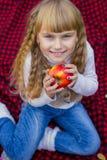 一个桃红色帽子的美丽的矮小的年轻婴孩用一个苹果在他的手上 漂亮的孩子坐红色格子花呢披肩 免版税库存图片
