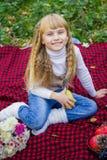 一个桃红色帽子的美丽的矮小的年轻婴孩用梨在手中 漂亮的孩子坐红色格子花呢披肩 库存图片