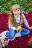一个桃红色帽子的美丽的矮小的年轻婴孩用梨在手中 漂亮的孩子坐红色格子花呢披肩 免版税库存图片