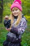 一个桃红色帽子的美丽的矮小的年轻婴孩用葡萄在他们的手上 免版税库存照片