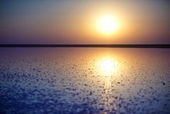 一个桃红色湖的盐和盐水,上色被微藻类Dunaliella盐沼在日落 库存图片
