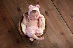 戴一个桃红色熊帽子的新出生的女孩 库存照片