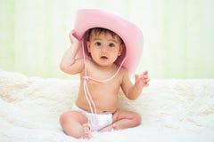 一个桃红色牛仔帽的婴孩在尿布坐长沙发 免版税图库摄影