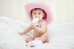 一个桃红色牛仔帽的婴孩在尿布坐长沙发 免版税库存照片
