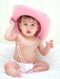 一个桃红色牛仔帽的婴孩在尿布坐长沙发 库存照片
