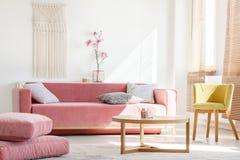 一个桃红色长沙发的真正的照片有站立在大pil旁边的枕头的 库存照片