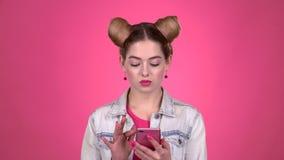 一个桃红色题目的女孩在电话打印一则消息 桃红色背景 股票录像