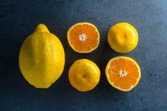一个桔子和一个柠檬的四个一半在一块蓝宝石 免版税库存照片