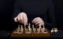 一个棋盘的特写镜头有棋形象的和手  库存图片