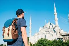 一个棒球帽的一个人有在蓝色清真寺旁边的一个背包的是著名视域在伊斯坦布尔 旅行,旅游业 免版税库存照片