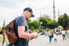 一个棒球帽的一个旅客有背包的看地图在蓝色清真寺-著名视域旁边  免版税图库摄影