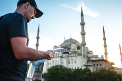 一个棒球帽的一个旅客有背包的看地图在蓝色清真寺-著名视域旁边  免版税库存照片