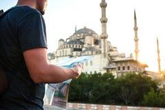 一个棒球帽的一个旅客有背包的看地图在蓝色清真寺-著名视域旁边  库存图片