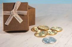 一个棕色礼物盒和一条米黄丝带与一个标签在光 库存图片