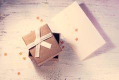 一个棕色礼物盒和一条米黄丝带与一个标记在轻的背景 圣诞节礼物 定调子 免版税库存照片