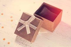 一个棕色礼物盒和一条米黄丝带与一个标记在轻的背景 圣诞节礼物 定调子 免版税库存图片