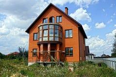 一个棕色私有砖房子的门面在有草的庭院里 库存图片
