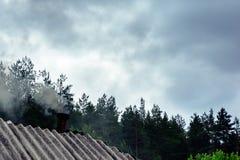 一个森林房子的屋顶有烟的 免版税库存照片