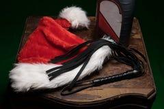 一个模糊的红色和白色圣诞老人帽子、一条黑鞭子和一个瓶机油,在老wodden桌,传播特别种类  库存图片