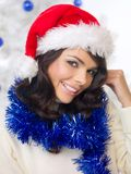 一个欢乐红色圣诞老人帽子的俏丽的妇女 库存照片