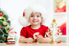 戴一个欢乐红色圣诞老人帽子的小女孩孩子 免版税库存照片