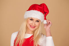 一个欢乐红色圣诞老人帽子的逗人喜爱的白肤金发的女孩 免版税库存照片