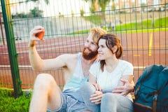 一个欧洲人` s对红色头发和胡子和妇女在演奏体育以后休息户外 人举行红色 图库摄影