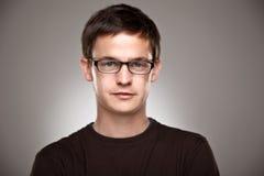 一个正常男孩的画象戴为装边的眼镜的在灰色背景 库存图片
