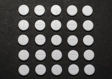 以一个正方形的形式白色圆的片剂在黑暗的背景 免版税库存照片