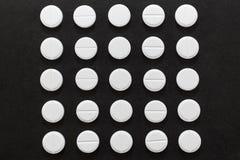 以一个正方形的形式白色圆的片剂在黑暗的背景 库存图片