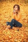一个正面女孩的秋天画象牛仔裤和一件毛线衣的本质上在一片落的黄色叶子的 库存照片