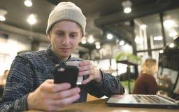 一个正面年轻人享用在咖啡馆的一个智能手机,当工作为膝上型计算机时 库存图片