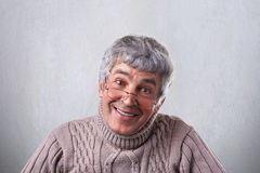 一个正面快乐的亲切的成熟亲切地看入照相机的人佩带的玻璃有柔和的微笑 微笑的老人,当立场时 库存照片